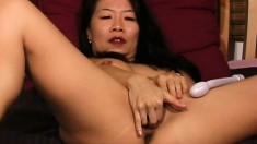 Naughty Asian cougar Silk Star drills her hairy peach with a sex toy