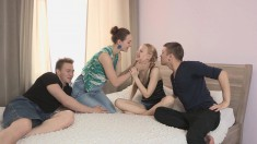 A pair of seductive girls play with each other and fuck two guys